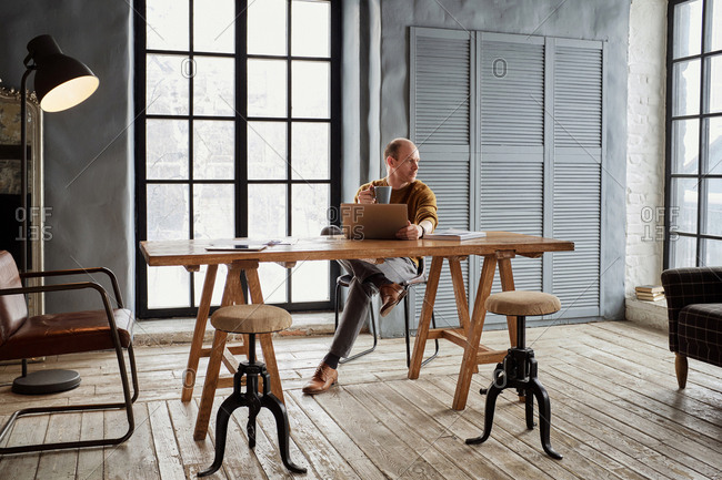 Middle-aged stylish bald man sitting at table in bright vintage office, drinking coffee and looking aside thoughtfully