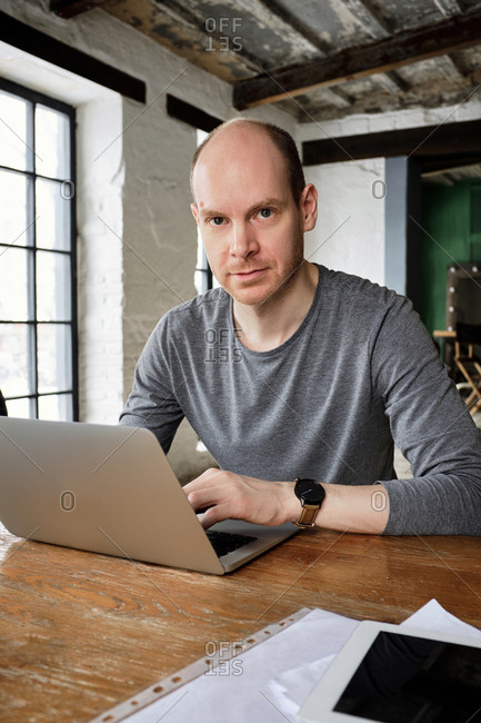 Portrait of middle-aged Caucasian male freelancer sitting in front of laptop in urban cafe and looking at camera