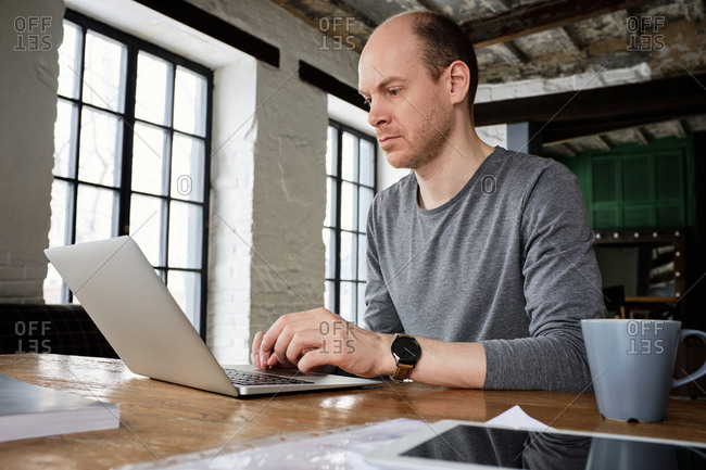 Middle-aged Caucasian businessman checking mail on laptop while sitting at wooden table in vintage cafe, low angle view