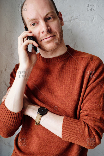 Portrait of confident middle-aged Caucasian man in stylish orange sweater standing against wall and talking on smartphone