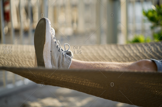 Close-up view of male feet in comfy canvas shoes lying in hammock