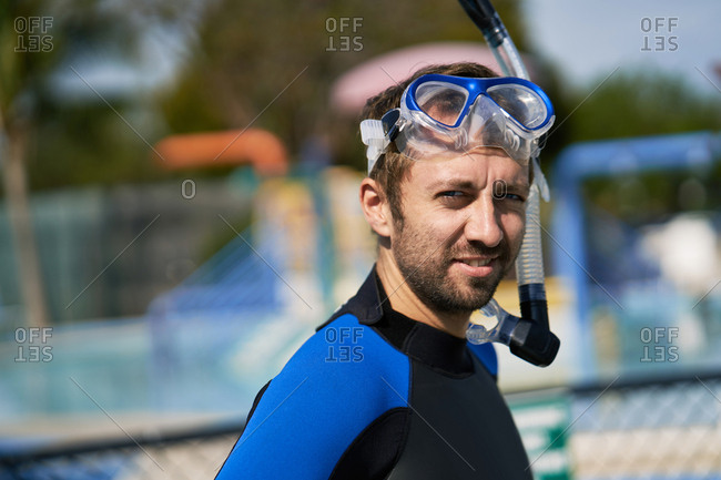 Professional snorkeler. Portrait of confident young man in diving suit with scuba mask and snorkel on his head looking at camera and smiling