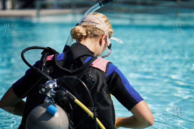 Rear view of blond woman in diving suit equipped with scuba mask, snorkel and aqualung getting ready to dive into swimming pool