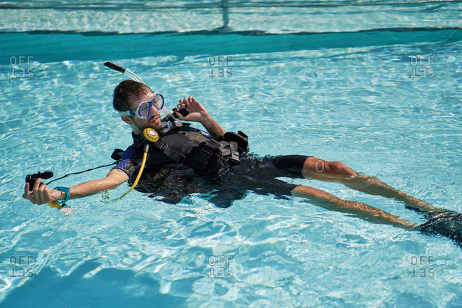 Diving instructor in swimming pool. Young dark-haired man in diving suit with professional diving equipment lying on his back in swimming pool and explaining basic scuba diving rules