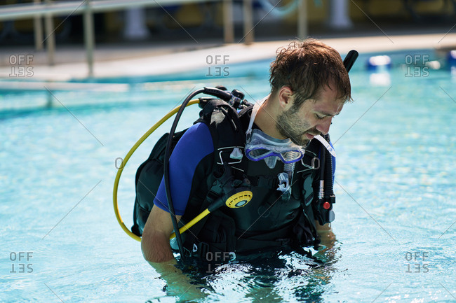 Beginning scuba diver in pool. Tired bearded man with full set of scuba diving gear leaving swimming pool after training