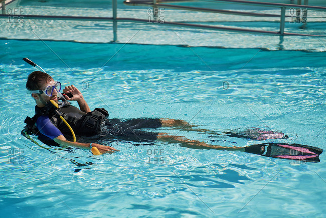Tourist taking diving lesson in pool. Young man in diving suit and swim fins, equipped with scuba, dive mask and snorkel lying on his back in swimming pool and waiting for instructor