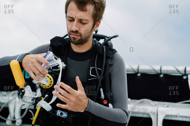 Concentrated male diver equipped with full set of scuba gear checking his silicone half mask before diving