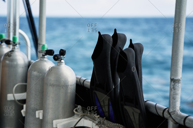 Equipment for underwater diving. View of scuba tanks and swim fins on boat against blue ocean background