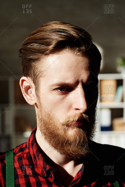 Portrait of handsome hipster.  Serious fair-haired young man with beard and moustache looking at camera, his face illuminated by sunlight