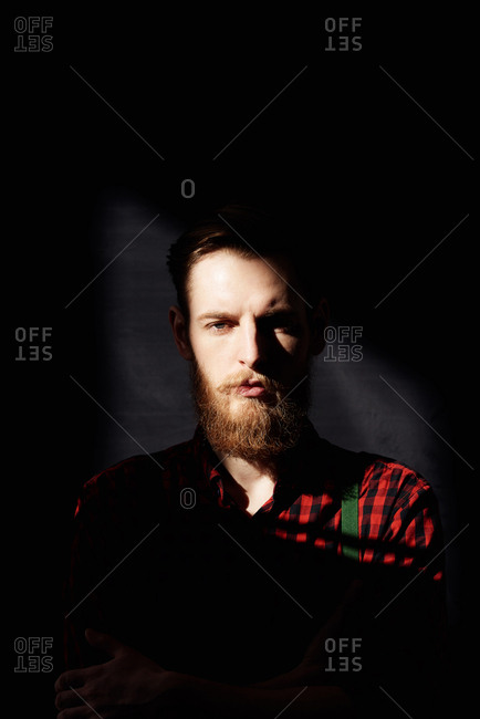 Portrait of young mysterious bearded hipster standing in dusky room and looking at camera piercingly, his face illuminated by sunlight