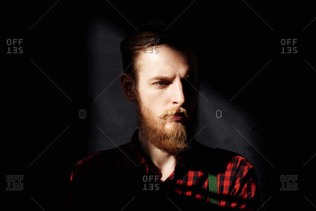 Portrait of young man with fair beard and moustache standing in dusky room and looking away pensively, sun lighting up his face