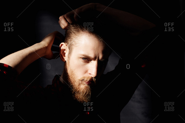 Portrait of young bearded man standing in dark room, smoothing his hair and looking at camera piercingly, his face illuminated by bright sun
