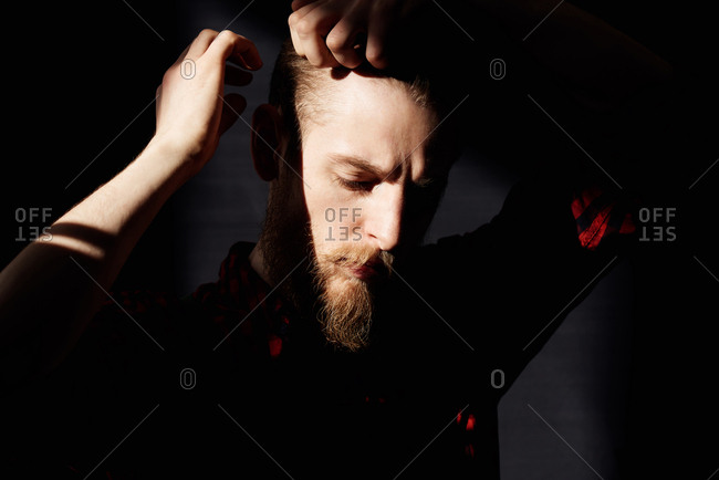 Portrait of young male hipster with fair beard and moustache looking down while touching his hair pensively in dusky room