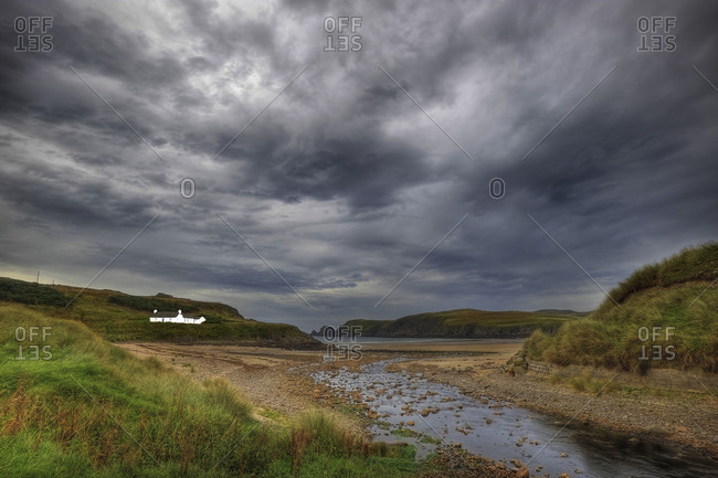 Lonesome house in a sea bay in Scottish highlands, a small brook lead to the sea.