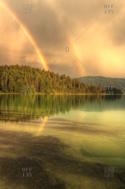HDR Recording of a double rainbow about the clear water of the Walchensee.