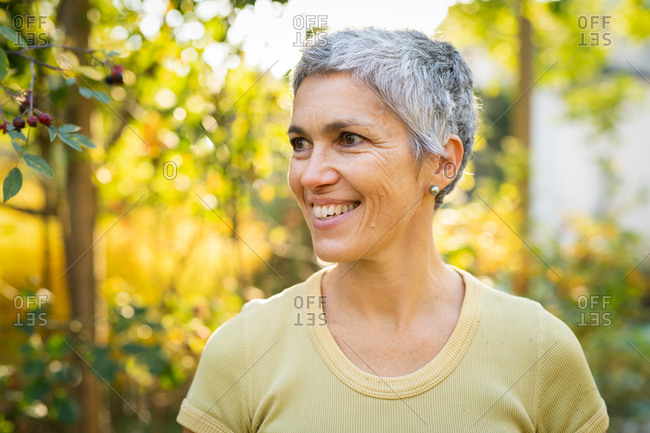 Portrait of a smiling woman with short gray hair outside in the autumn