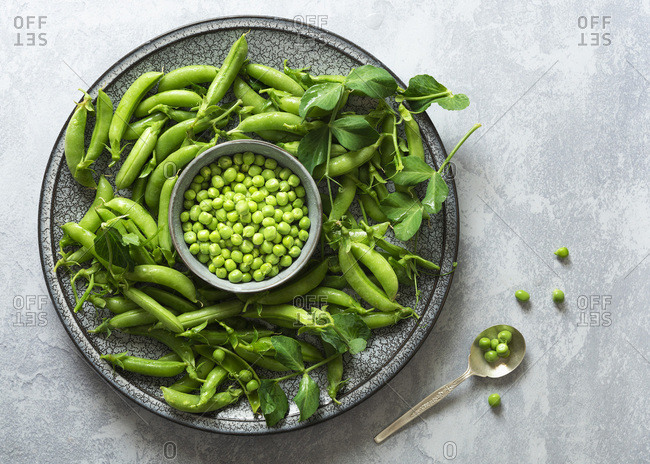 Green peas on a plate with a bowl of shelled peas.