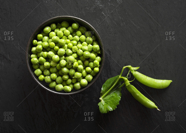 A bowl of fresh green peas with two pea pods.