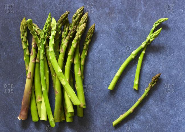 Fresh asparagus spears on a blue background.