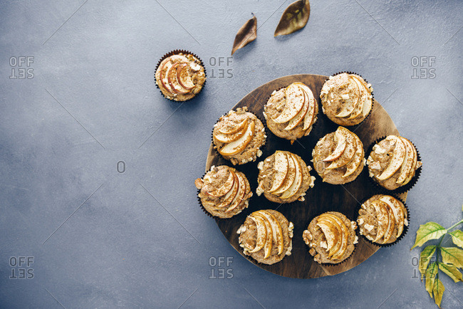 Apple muffins served on a wooden stand on a dark grey backdrop accompanied by fall leaves.