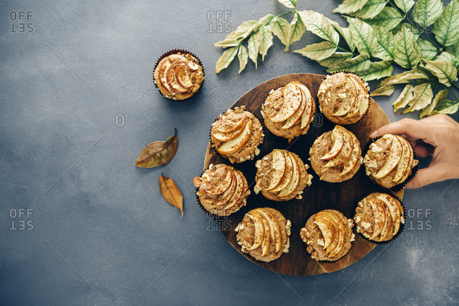 Apple muffins served on a wooden stand on a dark grey backdrop accompanied by fall leaves. A person grabbing one.