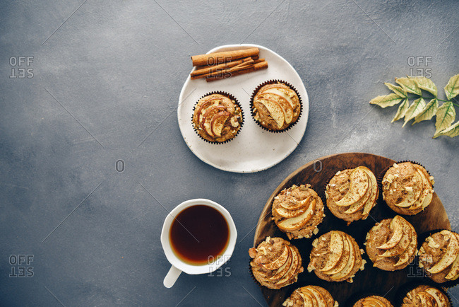 Apple muffins served on a wooden stand on a dark grey backdrop accompanied by fall leaves, a cup of tea, a plate and cinnamon sticks.