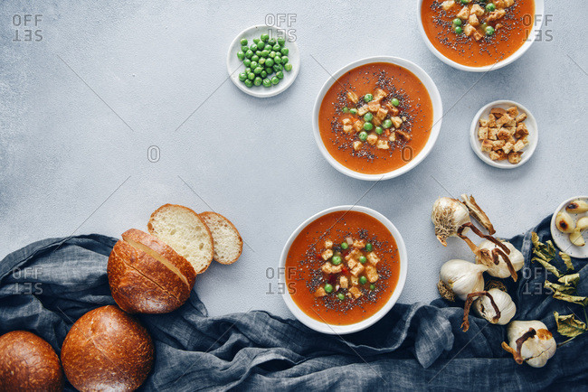 Vegan tomato soup served in three white bowls accompanied by bread rolls, roasted garlic, croutons and peas.