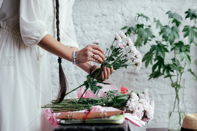 Hands of unrecognizable woman with a bride making flower bouquet.
