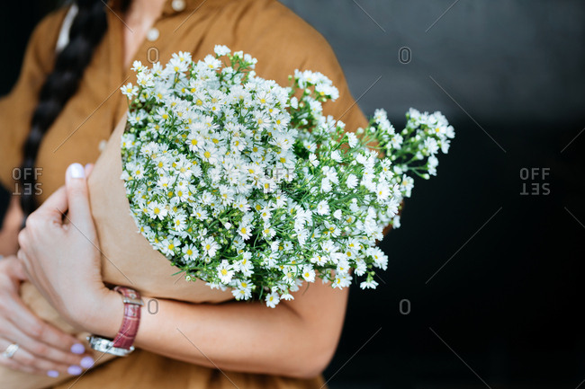 Hands of unrecognizable woman holding a bouquet.