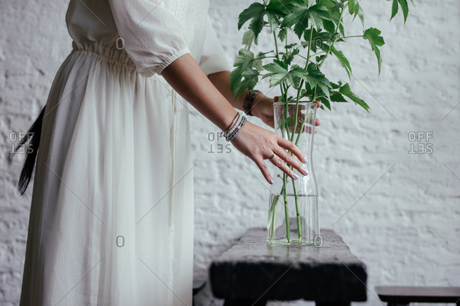 Hands of unrecognizable woman in a dress putting decorative leaf in a vase.