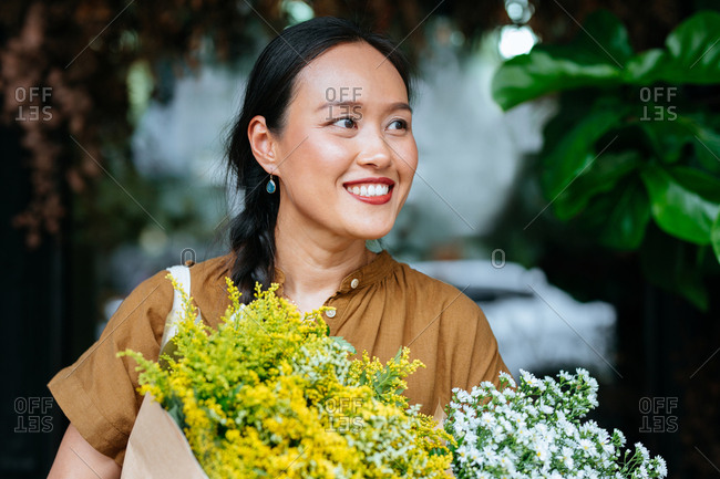 Portrait of smiling Asian woman standing outdoors and holding flowers.