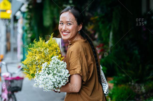 Beautiful Asian woman enjoying shopping outdoors and holding flowers.