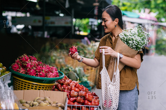 Beautiful smiling Thai woman picking a dragon fruit on outdoor food market.