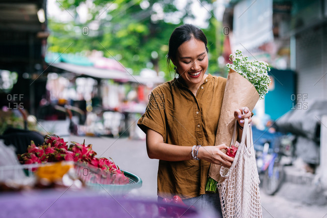 Beautiful smiling Thai woman shopping on food market.