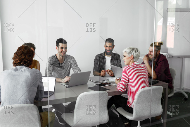Group of modern casual businessmen and businesswomen sitting together at meeting room and smiling.