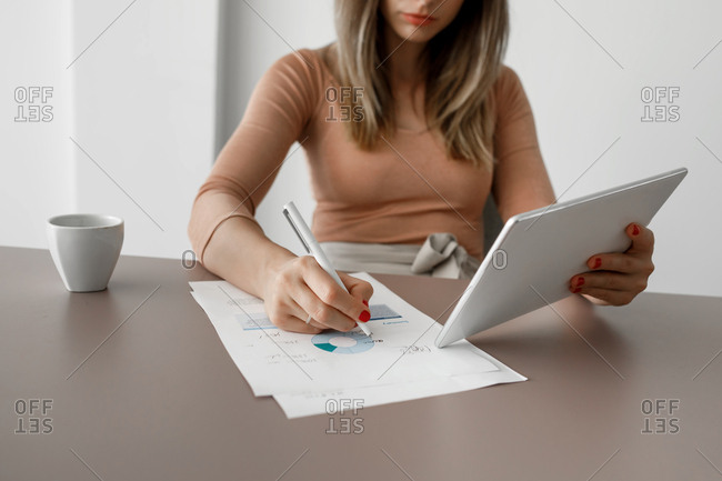 Hands of unrecognizable cropped  businesswoman holding tablet and writing on paper.