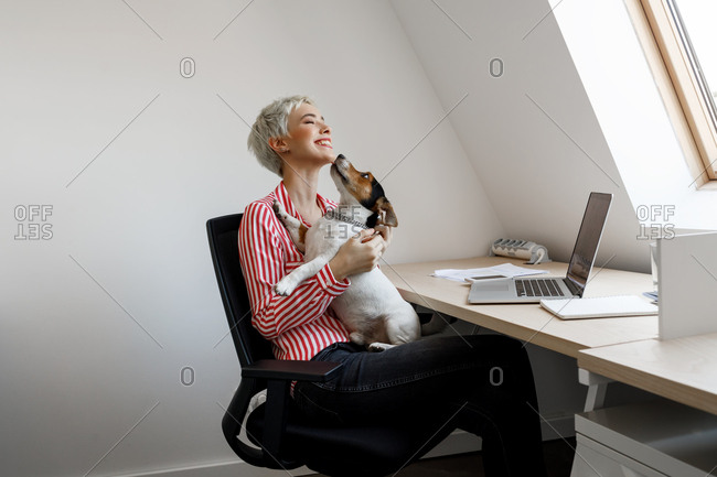 Young smiling businesswoman cuddling her dog pet at her office.