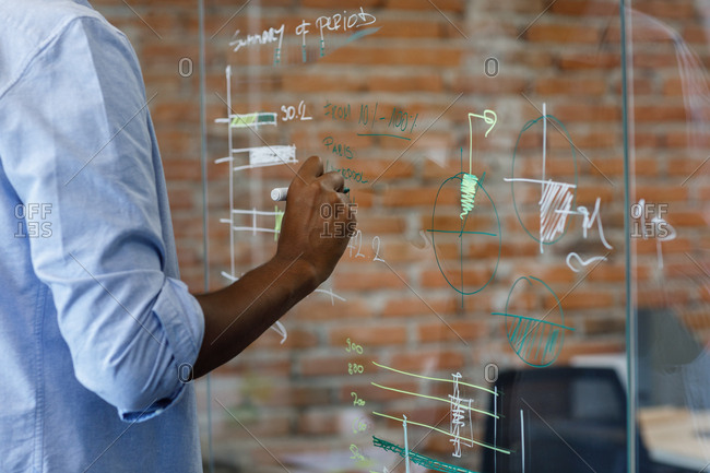 Hand of unrecognizable businessman writing data on glass board.