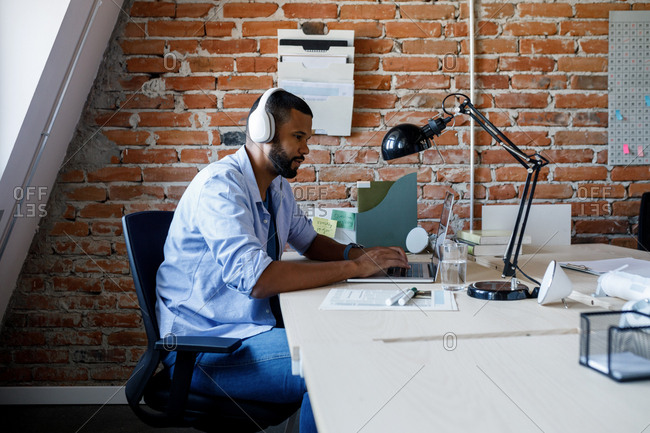 Young African businessman with headphones typing on his laptop at work.
