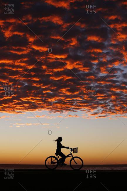Lone woman riding bike through?beach under moody sunset sky, La?Jolla, San Diego, California, USA