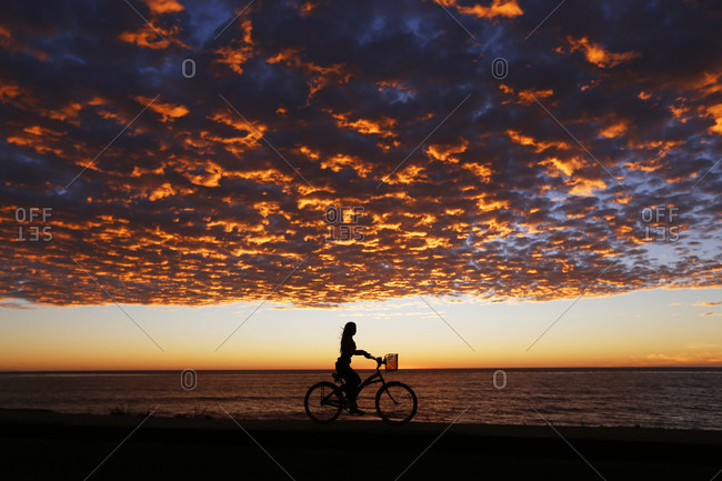 Woman riding bike through?beach under moody sunset sky, La Jolla, San Diego, California, USA