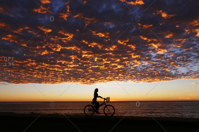 Woman riding bike through?beach under moody sunset sky, La Jolla, San Diego, California, USA