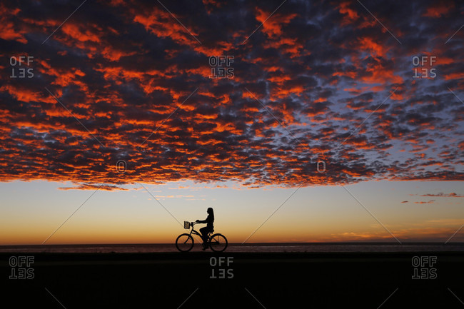 Lone woman riding silhouette horizon under moody sunset sky, La?Jolla, San Diego, California, USA