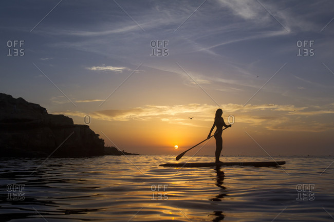 Side view of woman?paddle boarding?ion Pacific Ocean?at sunset, La?Jolla, San Diego, California, USA