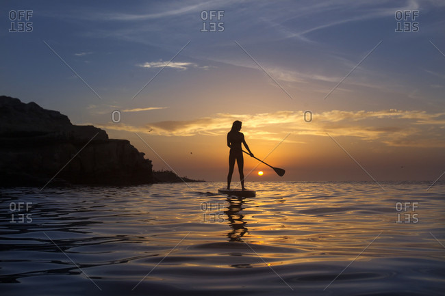 Rear view of woman paddle boarding on Pacific Ocean at sunset, San Diego, California, USA