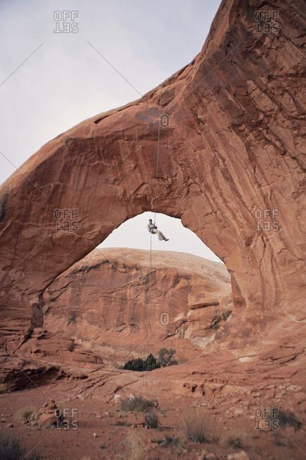 Rock climber hanging under eroded natural arch, Moab, Utah, USA