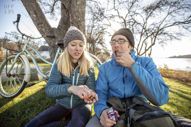 Young couple sitting on grass and sharing trail mix during break from bike ride, Portland, Maine, USA