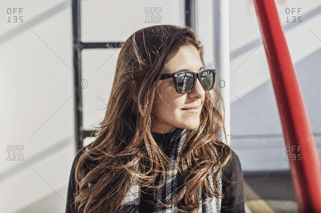 Portrait of smiling attractive young woman wearing sunglasses on ferry?