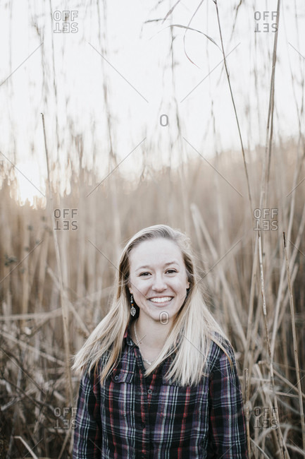 Laughing young woman standing in front of long grass in fall, Peaks Island, Maine, USA