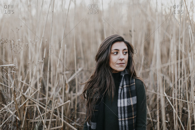 Young woman with scarf in front of long grass in fall, Portland, Maine, USA